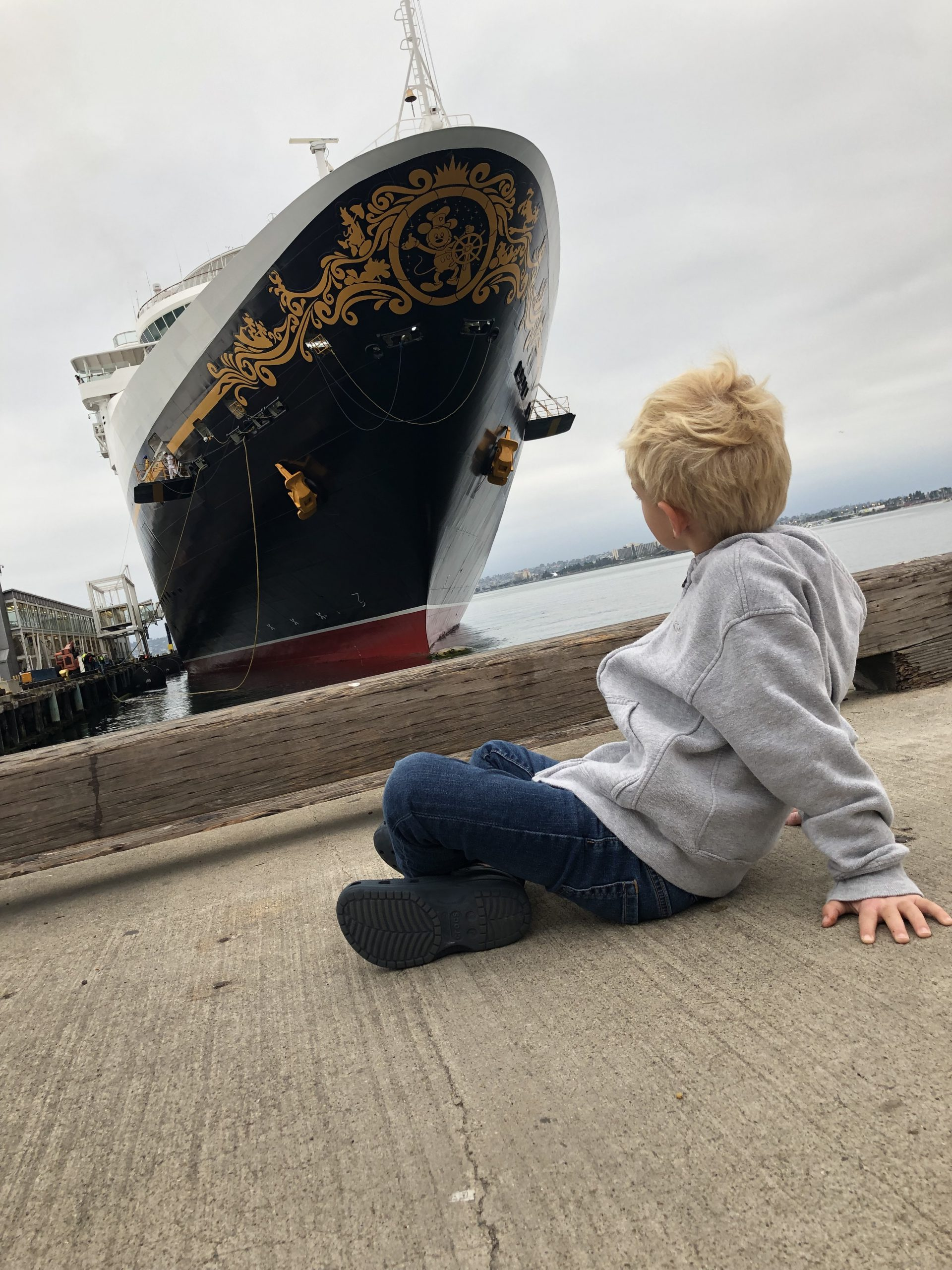 child sItting in front a large cruise ship