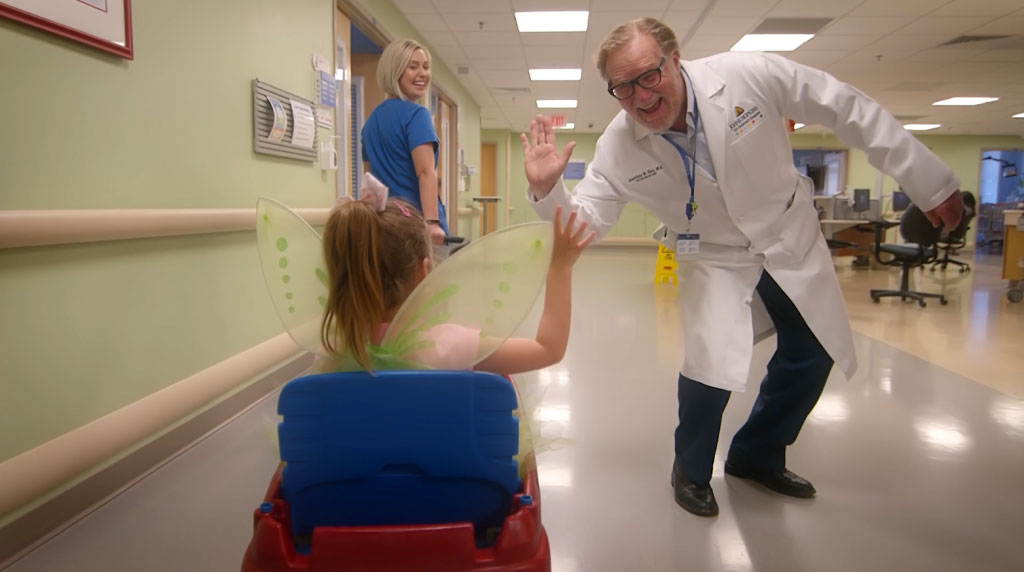 a Dr. High-fiving a young child
